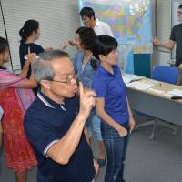 Japanese students practice using American Sign Language during a course by the Japanese ASL Signers Society in August in Tokyo's Chiyoda Ward. | KYODO