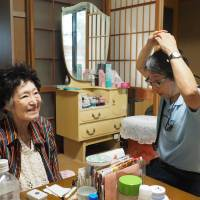 Dementia patient Etsuko Okizaki smiles after doctor Yoshimasa Takase makes a circle with his arms to indicate she is doing well Okizaki's home in Ota Ward, Tokyo, in September. | KYODO