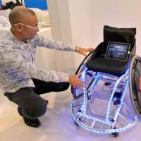 People Design Institute's Shinji Sudo looks at Wheelchair DJ, which has wheels that play music when spun and can be 'scratched' back and forth like a record. | YOSHIAKI MIURA