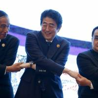 Indonesian President Joko Widodo (left), Prime Minister Shinzo Abe and Lao Prime Minister Thongsing Thammavong link hands during the 27th Association of Southeast Asian Nations summit in Kuala Lumpur on Sunday. | REUTERS