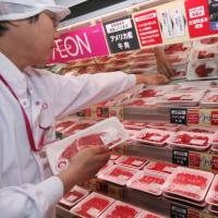A shop assistant displays American beef at an Aeon supermarket in Tokyo in this file image from 2008. Reductions in beef tariffs under the Trans-Pacific Partnership may bring down prices across the domestic beef market. | BLOOMBERG