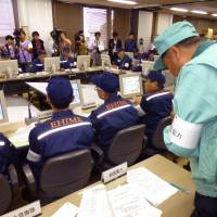 A Shikoku Electric Power Co. official speaks during a disaster drill held at the Ikata nuclear power plant in Ehime Prefecture on Sunday. | KYODO