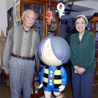 Artist Shigeru Mizuki (left) and his wife, Nunoe Mura, stand beside a figure of Kitaro, his most popular character, in May 2014 in his office in Chofu, western Tokyo. | KYODO