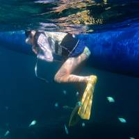 A tourist snorkels in the sea off the island of Ishigaki, Okinawa Prefecture, in June. | BLOOMBERG