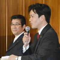 Hirofumi Yoshimura, who was projected to win Osaka's mayoral election, addresses a news conference in the city on Sunday as Osaka Gov. Ichiro Matsui, who also looked certain to win, looks on. | KYODO