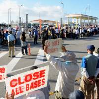 People raise signs in front of the U.S. Marine Corps' Camp Schwab in Nago, Okinawa Prefecture, Wednesday, calling for all U.S. bases in the prefecture to be closed. | KYODO