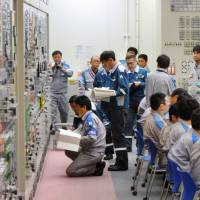 Final checks are conducted for reactor 2 in the central control room of Kyushu Electric Power Co.'s Sendai nuclear power plant in Satsumasendai, Kagoshima Prefecture, on Tuesday before the unit returned to full commercial operations. | POOL / KYODO