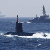The Maritime Self-Defense Force Soryu-class submarine Kokuryu sails past a vessel during a fleet review in Sagami Bay, off Yokosuka, Kanagawa Prefecture, on Oct. 18. | BLOOMBERG