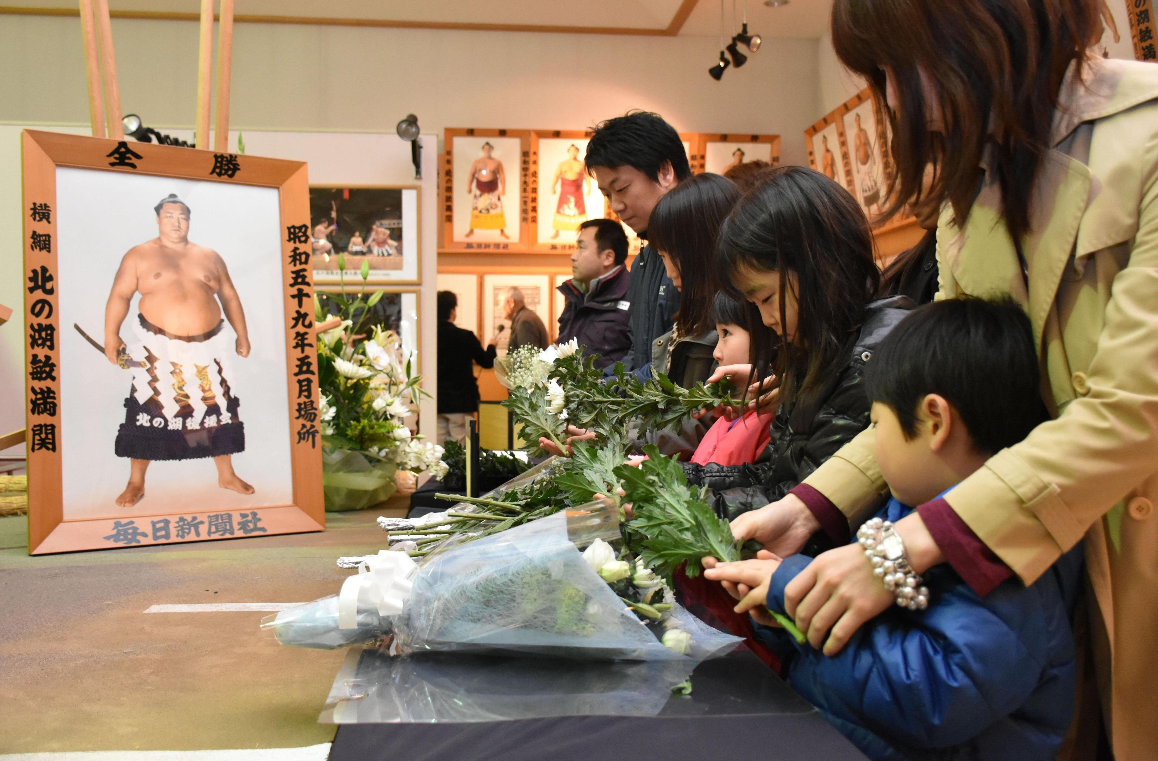 Visitors to the Kitanoumi Memorial Museum in the town of Sobetsu, Hokkaido, pay tribute Saturday to the wrestler. He died Friday in Fukuoka, where he was attending the Kyushu Grand Sumo Tournament.   KYODO