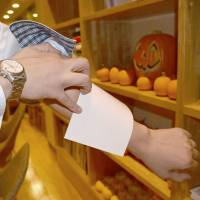A staffer at Ofuro Cafe utatane, a bathhouse in the city of Saitama, shows a sticker to cover tattoos on Oct. 21.   KYODO