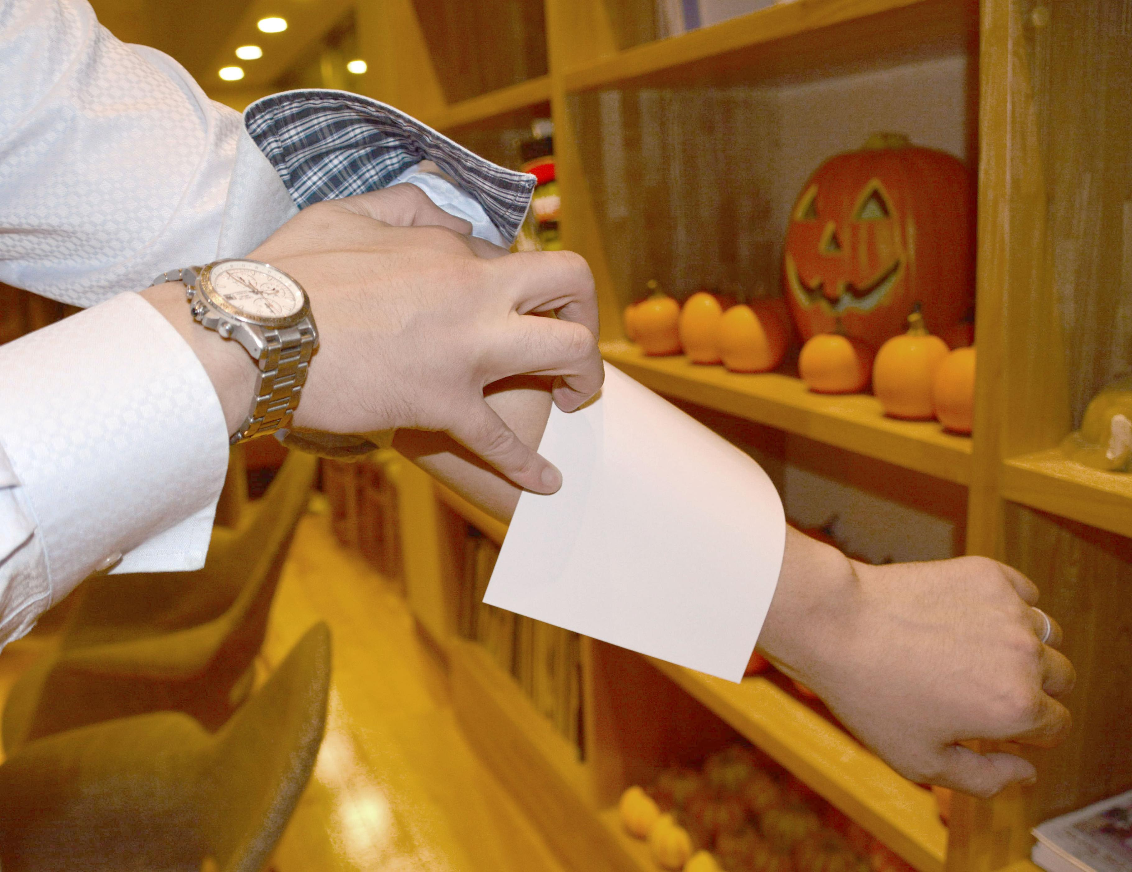 A staffer at Ofuro Cafe utatane, a bathhouse in the city of Saitama, shows a sticker to cover tattoos on Oct. 21. | KYODO