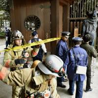 Firefighters and police officers investigate around the south gate at Yasukuni Shrine in central Tokyo on Monday morning after an explosion damaged a public restroom there. | KYODO