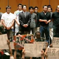 Strike one: Atsuya Furuta, then head of the Japan Professional Baseball Players Association union, stands with other Nippon Professional Baseball players as he addresses fans holding up messages in support of the players' strike on Sept. 19, 2004. | KYODO