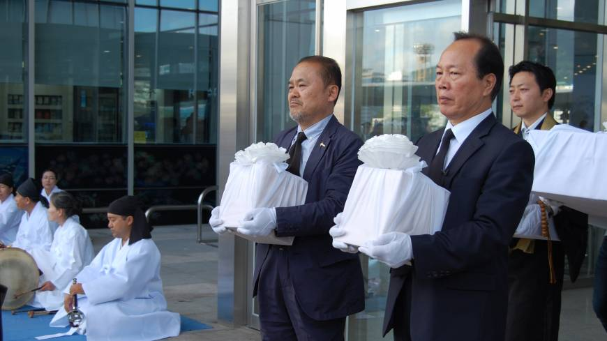 At Busan port on Sept. 18, Kim Gyeong-soo (right), the son of Lee Ok-sun, carries his uncle's remains alongside the relatives of a laborer who lost his life working at the Mitsubishi Bibai Coal Mine Hokkaido.  | KAYOKO KIMURA