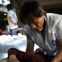 An MdM doctor checks on an evacuee at an emergency shelter following the Tohoku quake of March 11, 2011. | MDM/ERIC RECHSTEINER