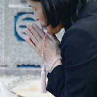False accusation: Keiko Aoki prays at the grave of her daughter in Nara after being released from prison. Aoki, along with her partner Tatsuhiro Boku, was convicted of murdering her daughter in 1995. An upcoming retrial is expected to show that the couple were coerced into confessing to the crime. | KYODO