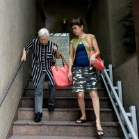 Dealing with dementia: Akiko Sakai (right) walks with her mother, Asayo, a former nurse and housewife who has been diagnosed with Alzheimer's disease. | BLOOMBERG