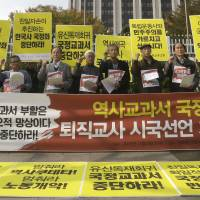 A matter of history: Retired South Korean teachers shout slogans during a rally against the revision of the publication system for Korean history textbooks in front of the government complex in Seoul last week. | AP