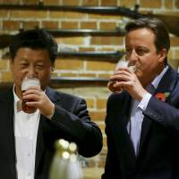 Down one for diplomacy: Chinese President Xi Jinping (left) drinks a beer with British Prime Minister David Cameron at a pub in England last month. | REUTERS