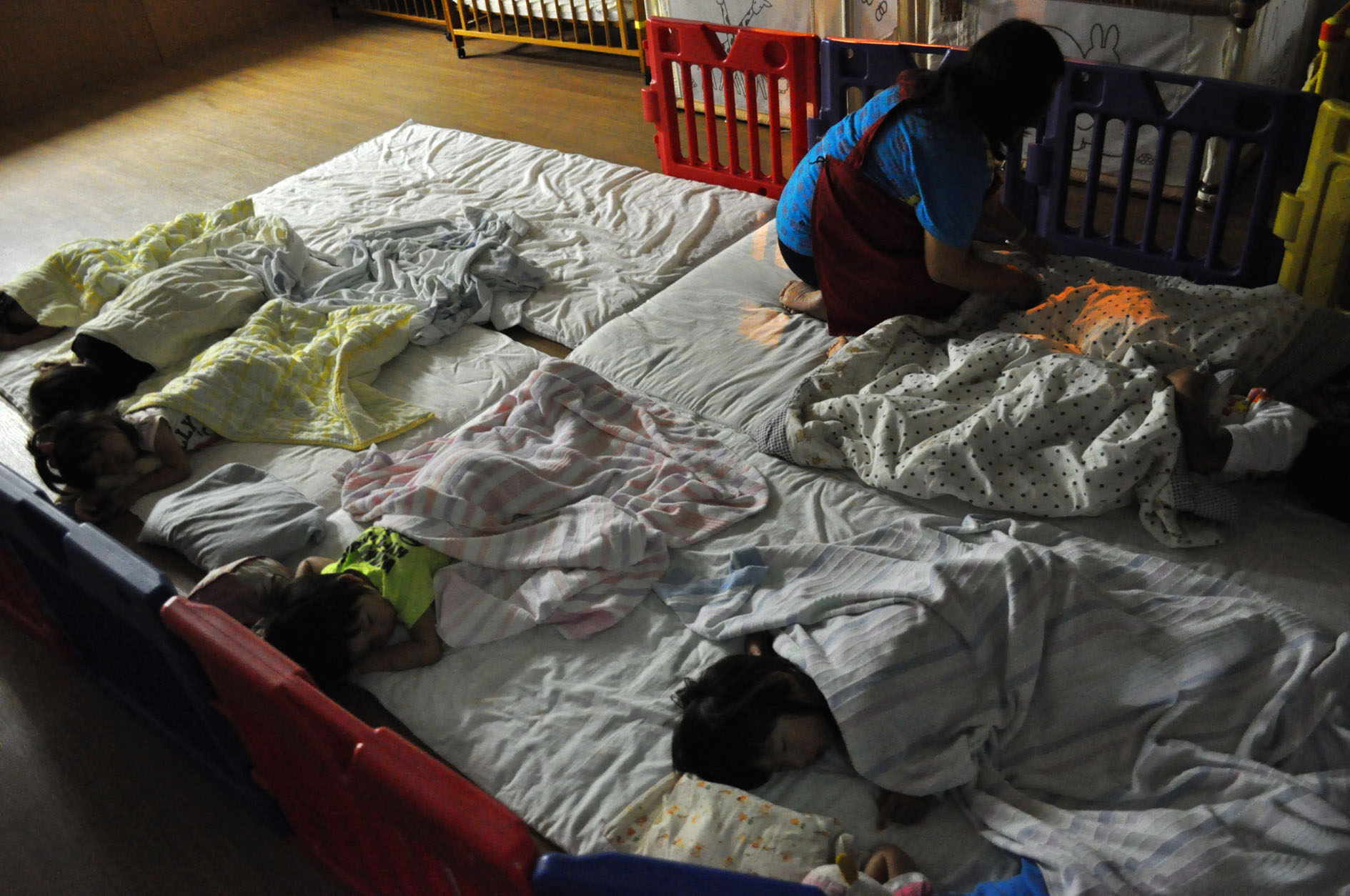 Slumber party: Children sleep late at night at an unlicensed 24-hour nursery supporting single mothers in Osaka. Many single moms have two or more jobs.   KYODO