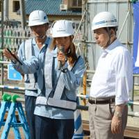 Social construct: An engineer working on the Tokyo Gaikan Expressway explains the project to Akihiro Ota (right), then the infrastructure minister, in 2014. Channelling working women into sectors where there are labor shortages, such as construction, will be vital if Japan is to have any hope of meeting Prime Minister Shinzo Abe's ambitious growth target.  | KYODO