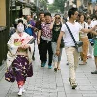 Tourists look on as a maiko — an apprentice geisha —walks past in the Gion area of Kyoto. | BLOOMBERG