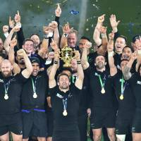 New Zealand's flanker and captain, Richie McCaw, holds the Webb Ellis Cup as he celebrates with teammates after winninng the final match of the 2015 Rugby World Cup between New Zealand and Australia at Twickenham stadium, southwest London, on Saturday. | AFP-JIJI
