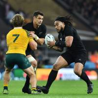 New Zealand center Ma'a Nonu runs with the ball as Australia's flanker Michael Hooper blocks New Zealand's fly half Dan Carter during the final match of the 2015 Rugby World Cup between New Zealand and Australia at Twickenham stadium, southwest London, on Saturday. | AFP-JIJI