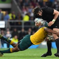 New Zealand lock Sam Whitelock is tackled by Australia's prop Sekope Kepu during the final match of the 2015 Rugby World Cup between New Zealand and Australia at Twickenham stadium, southwest London, on Saturday. | AFP-JIJI