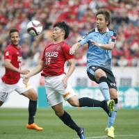 Urawa's Yuki Muto (left) vies for the ball with Kawasaki's Yuto Takeoka in J.League action at Saitama Stadium on Saturday. The match ended in a 1-1 draw. | KYODO