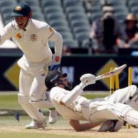 New Zealand's Mitchell Santner falls over after being stumped by Australia wicketkeeper Peter Nevill (left) during the third day of the third test in Adelaide, Australia, on Sunday. | REUTERS