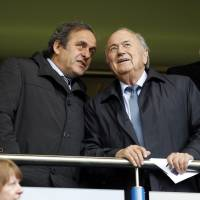 UEFA president Michel Platini (left) and FIFA president Sepp Blatter talk at a match in London in this May 2013 file photo. | AFP-JIJI
