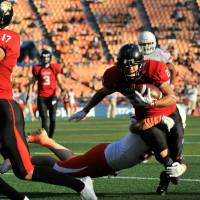 Fujitsu Frontiers wide receiver Jumpei Yoshimoto is tackled by a Lixil Deers defender in Sunday's game at Yokohama Stadium. The Frontiers finished the season with a perfect 7-0 record. | HIROSHI IKEZAWA
