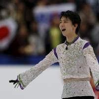 Yuzuru Hanyu reacts after his free skate on Saturday at Nagano's Big Hat. Hanyu earned a world-record score of 216.07 points in the free skate a day after shattering his own global mark in the short program. | REUTERS