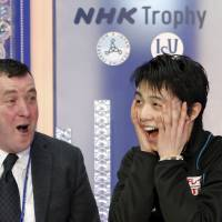 Yuzuru Hanyu (right) and his coach Brian Orser celebrate his winning performance in the men's free skate on Saturday at Nagano's Big Hat. | REUTERS