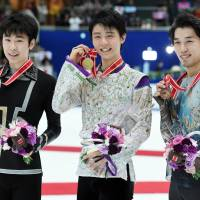 Men's singles winner Yuzuru Hanyu  (center) poses with runner-up Jin Boyang of China (left) and third-place finisher Takahito Mura on the podium during the NHK Trophy on Saturday in Nagano. | AFP-JIJI