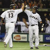 Japan's Sho Nakata celebrates with catcher Motohiro Shima after scoring on a single by left fielder Ryosuke Hirata during the fourth inning of their Premier 12 semifinal game against South Korea on Thursday at Tokyo Dome.   AP