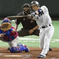 Samurai Japan's Motohiro Shima delivers a game-winning single in the ninth inning against Puerto Rico in Friday's exhibition contest in Fukuoka. Japan edged Puerto Rico 3-2. | KYODO