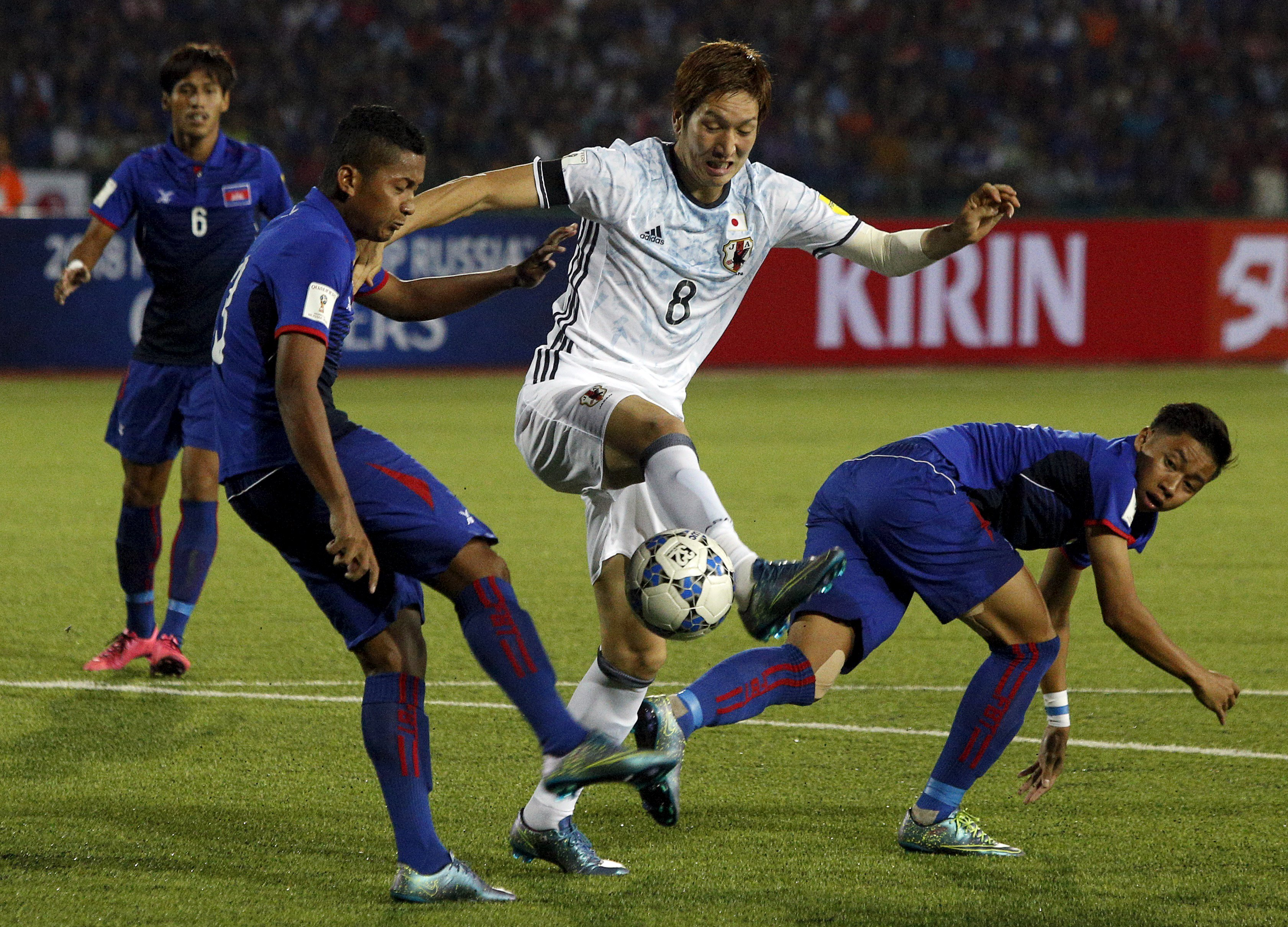 Japan's Genki Haraguchi (center) takes on the Cambodia defense during Japan's 2-0 World Cup qualifying win in Phnom Penh on Tuesday. | REUTERS