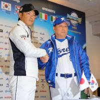 Samurai Japan manager Hiroki Kokubo and South Korea skipper Kim In-sik shake hands after a news conference on Saturday in Sapporo. | KAZ NAGATSUKA