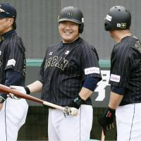 Slugger Takeya Nakamura (center) and his Samurai Japan teammates share a light moment during Tuesday's practice in Taipei. Japan takes on Mexico in a Premier 12 game on Wednesday at Tien-Mou Stadium. | KYODO