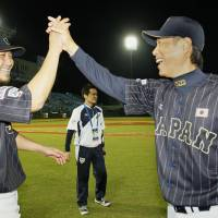Japan manager Hiroki Kokubo (right) high fives infielder Sho Nakata after their victory over the United States during the Premier 12 on Saturday. | KYODO
