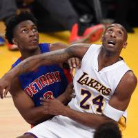 The Lakers' Kobe Bryant (right) competes against the Pistons' Stanley Johnson for a rebound during their game on Sunday in Los Angeles. | AFP-JIJI