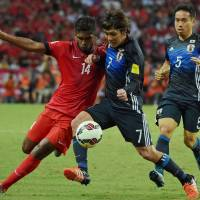 Singapore's Hariss Harun (left) and Japan's Yosuke Kashiwagi vie for the ball as Yuto Nagatomo watches during their second-round Asian qualifier in Singapore on Thursday. Japan defeated Singapore 3-0. | AP