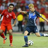 Japan's Keisuke Honda takes a shot during Thursday's match against Singapore. He had a goal in Japan's 3-0 triumph. | KYODO