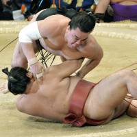Yokozuna Harumafuji manhandles Yoshikaze at the Kyushu Grand Sumo Tournament on Thursday in Fukuoka. | KYODO