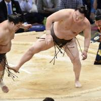 Hakuho (right) watches as opponent Myogiryu goes out of the ring during their bout at the Kyushu Grand Sumo Tournament on Sunday.   KYODO