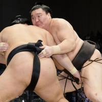 Hakuho (right) gets to grips with Goeido at the Kyushu Grand Sumo Tournament in Fukuoka on Monday.   KYODO