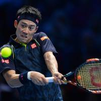 Kei Nishikori plays a shot from Roger Federer during their round-robin match at the ATP World Tour Finals on Thursday. | AP