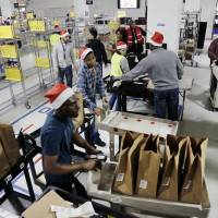 Amazon Prime employees push carts with bags loaded with goods for delivery to customers at the company's urban fulfillment facility Dec. 22 in New York. | AP